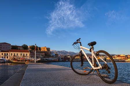 Early morning in Old Venetian port, Chania, Crete, Greece. Close-up of bicycle on pier. Bicycle tours, cycling, sightseeing. Healthy lifestyle, rides.