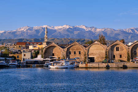Fishing boats anchored by piers of Old Venetian shipyards or Neoria. Church bell tower and minaret, distant Cretan mountain. Chania, Crete, Greece.