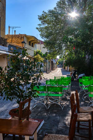 Early morning in empty narrow streets of old mediterranean town. Bright sunlight. Street cafe furniture in foreground. Chania, Crete, Greece