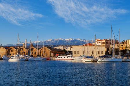 Old Venetian port, Chania, Crete, Greece. Sailboats, yachts, pier, shipyards or Arsenali Veneziani or Neoria. Bell tower and minaret, Cretan mountains