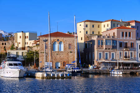 Sailing boats anchored by piers of Old Venetian harbour and Grand Arsenal, Venetian shipyard, in Chania, Crete, Greece.