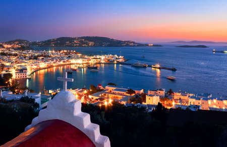 Beautiful view Mykonos, Greece after sunset, Greek Orthodox church, ships, whitewashed houses. Town lights up. Vacations, Mediterranean lifestyle