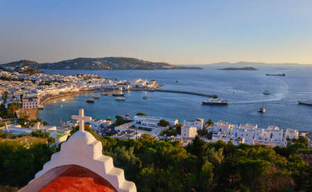 Beautiful sunset of Mykonos, Cyclades, Greece, Greek Orthodox church, ships, port, whitewashed houses, vacation, leisure, Mediterranean lifestyle