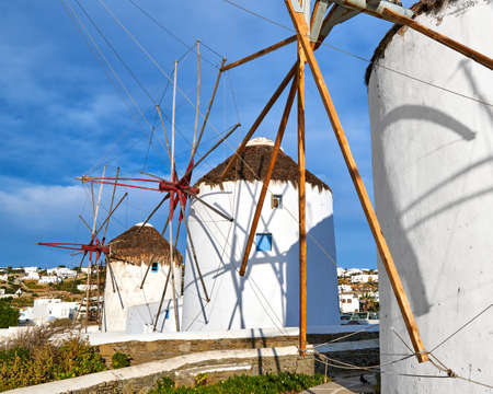 Famous tourist attraction of Mykonos, Greece. Traditional whitewashed windmills, summer, blue sky, beautiful clouds. Travel destination, iconic view. Archivio Fotografico