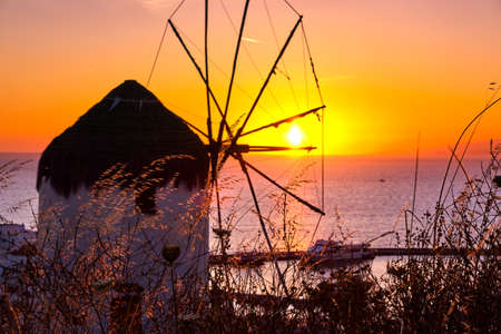 Famous traditional Greek windmill, Mykonos, Greece against sunset. Beautiful sky, sun touch sea horizon, high grass in foreground, colorful image.