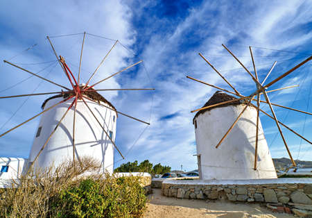 Famous tourist attraction of Mykonos, Greece. Two traditional whitewashed windmills at day. Summer, blue sky, beautiful clouds. Travel destination
