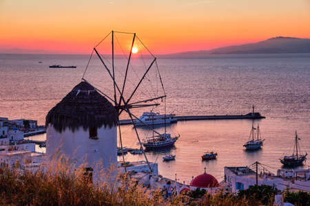 Famous traditional Greek windmill over port of Mykonos, Greece at sunset. Beautiful sky, sun touch sea horizon, boats, pier, high grass in foreground.