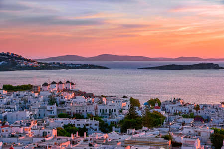 Beautiful sunset view of famous white windmills on hill top, Mykonos, Greece. Colorful sunset sky, summer, iconic destination, Mediterranean landscape