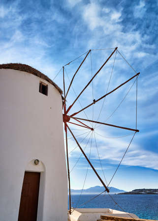 Famous tourist attraction of Mykonos, Greece. Traditional whitewashed windmill by sea. Summer, blue sky. Travel destination, iconic view. Rear upshot Archivio Fotografico