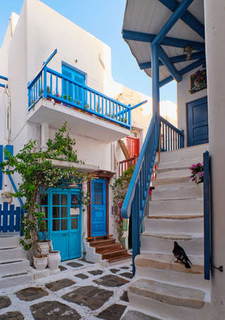 Traditional narrow cobbled streets, beautiful alleyways of Greek island towns. White houses, flower pots, blue balconies and doors. Mykonos, Greece Archivio Fotografico