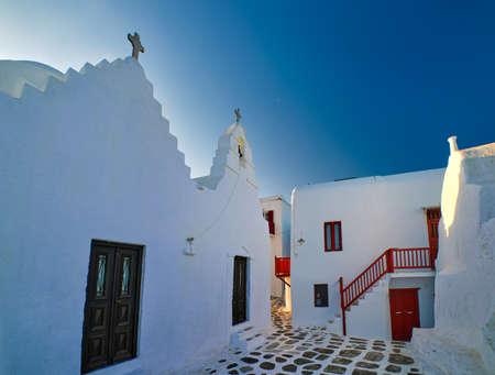 Famous tourist landmark, Mykonos island, Greece. Entrance to white Greek Orthodox church of Panagia Paraportiani. whitewashed walls, deep blue sky Archivio Fotografico