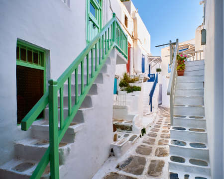 Romantic traditional narrow alleyways of Greek island towns. White houses, flower pots, colorful balconies and doors. Mykonos, Greece