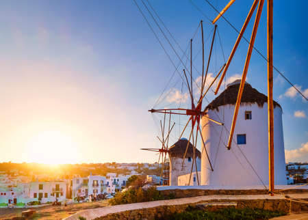 Famous tourist attraction of Mykonos, Greece. Traditional whitewashed windmills in row against sun. Summer, sunrise, travel destination, iconic view. Archivio Fotografico