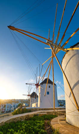 Famous tourist attraction of Mykonos, Greece. Traditional whitewashed windmills. Summer, sunrise, blue sky. Travel destination, iconic view. Upshot