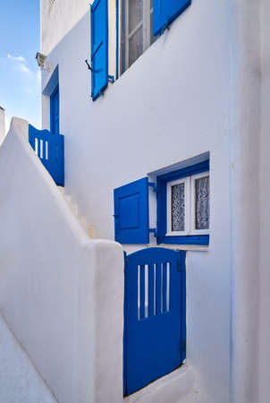 Traditional Greek house on Cyclades or Aegean islands. Whitewashed walls and dark blue doors, shutters and window frames. Colors of Greece.