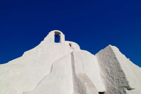 Famous tourist landmark, Mykonos island, Greece. White Greek Orthodox church of Panagia Paraportiani at sunrise. Upshot, white church, deep blue sky Archivio Fotografico