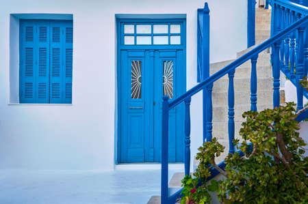 Traditional Greek porch, whitewashed walls, blue shutters, doorway and doors, banisters of street stairs. Mediterranean island unique design.