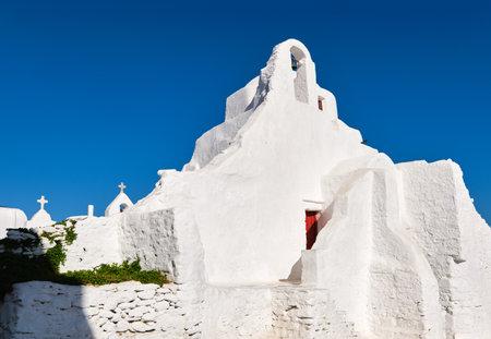 Iconic tourist landmark, Mykonos, Greece. White Greek Orthodox church of Panagia Paraportiani, town of Chora on island at sunrise. Iconic destination Archivio Fotografico