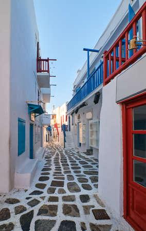Beautiful traditional narrow alleyways of Greek island towns. White houses, flower pots, blue balconies and doors. Mykonos, Greece Archivio Fotografico
