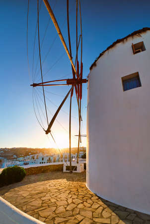 Famous tourist attraction of Mykonos, Greece. Traditional whitewashed windmill. Summer, sunrise, blue sky. Travel destination, iconic view. Upshot
