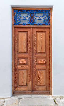 Old vintage wooden doors in light natural color decorated with blue forge-smithing metal ornament with monograms of capital letters M and X