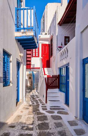 Beautiful traditional alleyways of Greek island towns. White walls, colorful balconies and doors, cobblestone street, morning sun. Mykonos, Greece