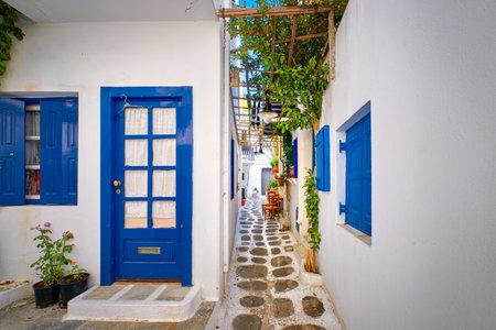 Beautiful traditional narrow alleyways of Greek island towns. White houses, flower pots, blue windows and doors. Mykonos, Greece Archivio Fotografico