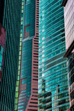 Details of close standing downtown buildings. Vertical lines, rhythm, reflections, cyan and reddish colors. Concept of business district architecture