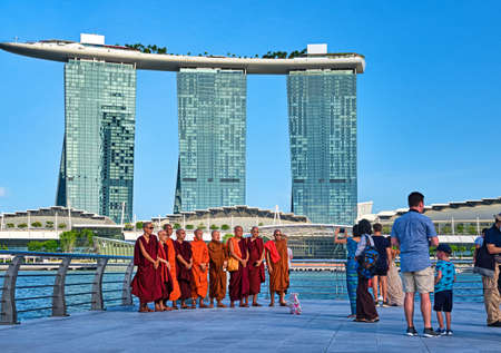 Singapore - Feb 25, 2020. Buddhist monks stand for group photo with iconic Marina Bay Sands in background. Tourists wait around for their turn.