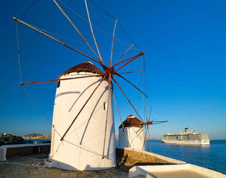 Famous tourist attraction of Mykonos, Greece. Traditional whitewashed windmills by sea and cruise liner leaving port. Morning, summer, clear blue sky