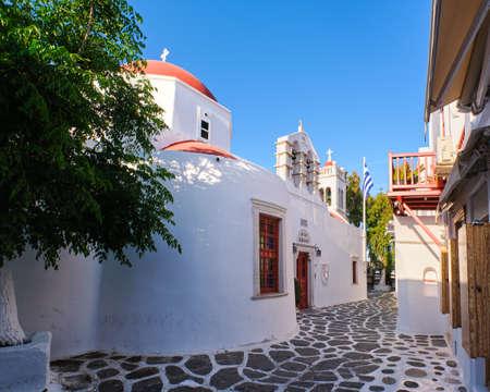 Traditional Greek Orthodox church in Greek island town. Red dome, whitewashed walls, Greek flag and bell tower. Mykonos, Cyclades, Greece. Archivio Fotografico