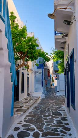 Beautiful traditional alleyways of Greek island towns. White walls, blue balconies and doors, cobblestone street, morning sun. Mykonos, Greece Archivio Fotografico