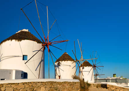 Famous tourist attraction of Mykonos, Greece. Traditional whitewashed windmills, summer, blue sky, cruise liner. Travel destination, iconic view.