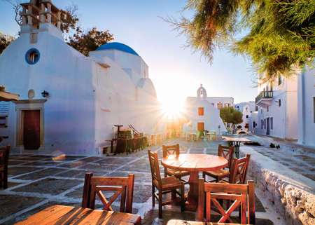 Sunrise in alleyways of Mykonos, Greece. Greek whitewashed churches in small town square, street cafe tables and chairs, sun and lens flares.