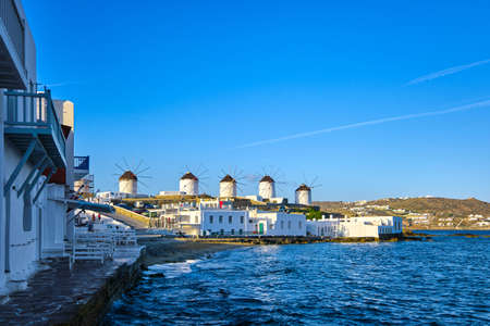 Beautiful view of famous traditional white windmills on hill top, Mykonos, Greece. Whitewashed houses, summer, morning, sea, iconic destination