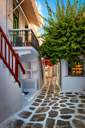 Beautiful traditional narrow cobbled streets of Greek island towns. Whitewashed houses, souvenir shops, morning summer sunshine. Mykonos, Greece. Archivio Fotografico