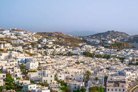 Beautiful view of Chora town of Mykonos at sunset, Greece. Whitewashed houses, hills, greenery, seafront, famous windmills.