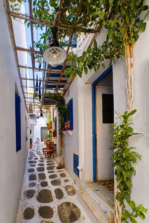 Beautiful traditional alleyways of Greek island towns. White walls, blue balconies and doors, cobblestone street, vines. Mykonos, Greece