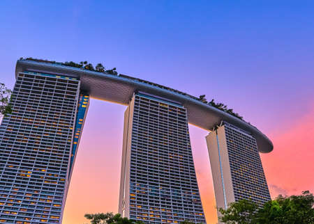 Rear view upshot of part Marina Bay Sands hotel and casino against colorful tropical sunset, Singapore. Iconic tourist attraction, luxury vacations