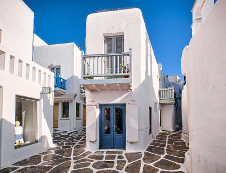 Traditional narrow cobbled streets, beautiful alleyways of Greek island town. Whitewashed houses, shop, cafe, morning summer sunshine. Mykonos, Greece Archivio Fotografico