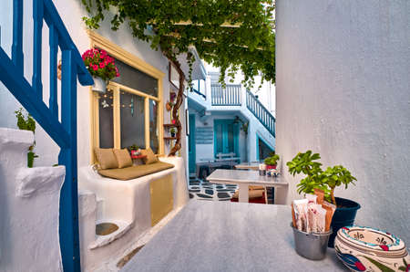 Traditional narrow cobbled streets, beautiful lanes of Greek island towns. Whitewashed houses, cafes, tables, chairs, stairs, doors. Mykonos, Greece