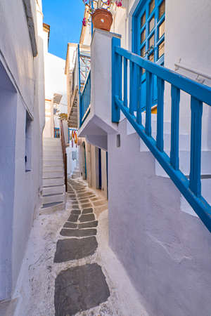 Traditional narrow cobbled streets, beautiful alleyways of Greek island towns. White houses, flower pots, balconies, stairs and doors. Mykonos, Greece