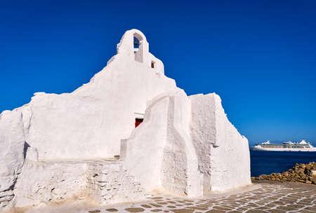 Famous tourist landmark, Mykonos, Greece. White Greek Orthodox church of Panagia Paraportiani, town of Chora on island at sunrise. Iconic destination Archivio Fotografico