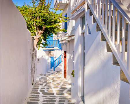 Traditional narrow cobbled streets, beautiful alleyways of Greek island town. Whitewashed houses, olive trees, blue balconies, stairs. Mykonos, Greece