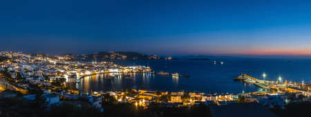 Beautiful night panorama of Mykonos, Greece, ships, port, whitewashed houses. Town lights up. Vacations, leisure, nightlife, Mediterranean lifestyle