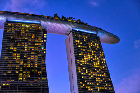 Rear view upshot of part of Marina Bay Sands hotel, colorful tropical twilight, Singapore. Famous tourist attraction, underexposed, low-light