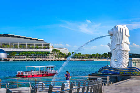Tourist boat pass by Merlion, symbol of Singapore, on Marina Bay shore. A couple of unrecognizable adults take pictures or makes selfies with a view