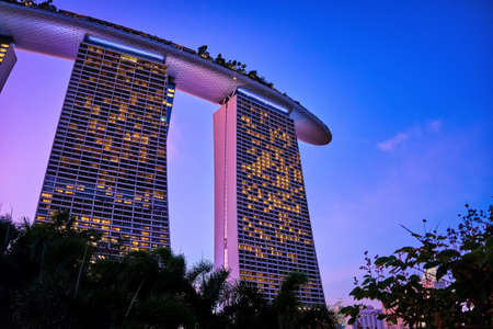 Rear view upshot of part Marina Bay Sands and colorful tropical sunset and above trees, Singapore. Famous tourist attraction, twilight deep colors. Editoriali