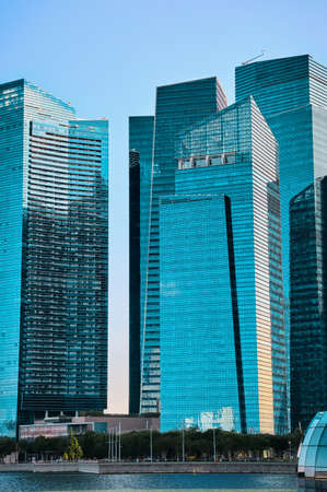 Group of buildings in CBD or Central Business District over Marina Bay waters in day light, Singapore. Vertical shot in cyan colors.