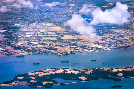 Aerial view of coastal construction or port areas in Strait of Malacca, on airplane route to Malaysia or Singapore. Airplane shot